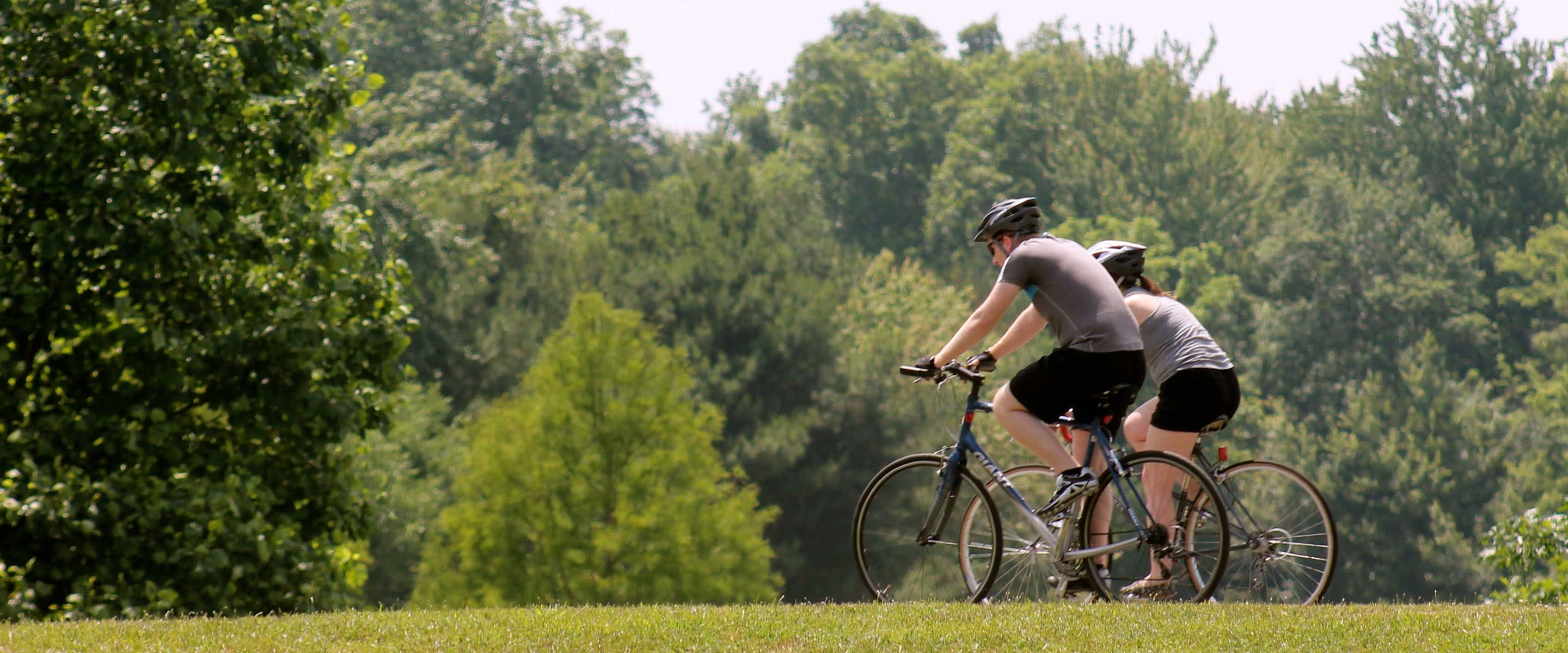 A couple enjoying a bike ride on a paved trail at Buffalo Trace Park
