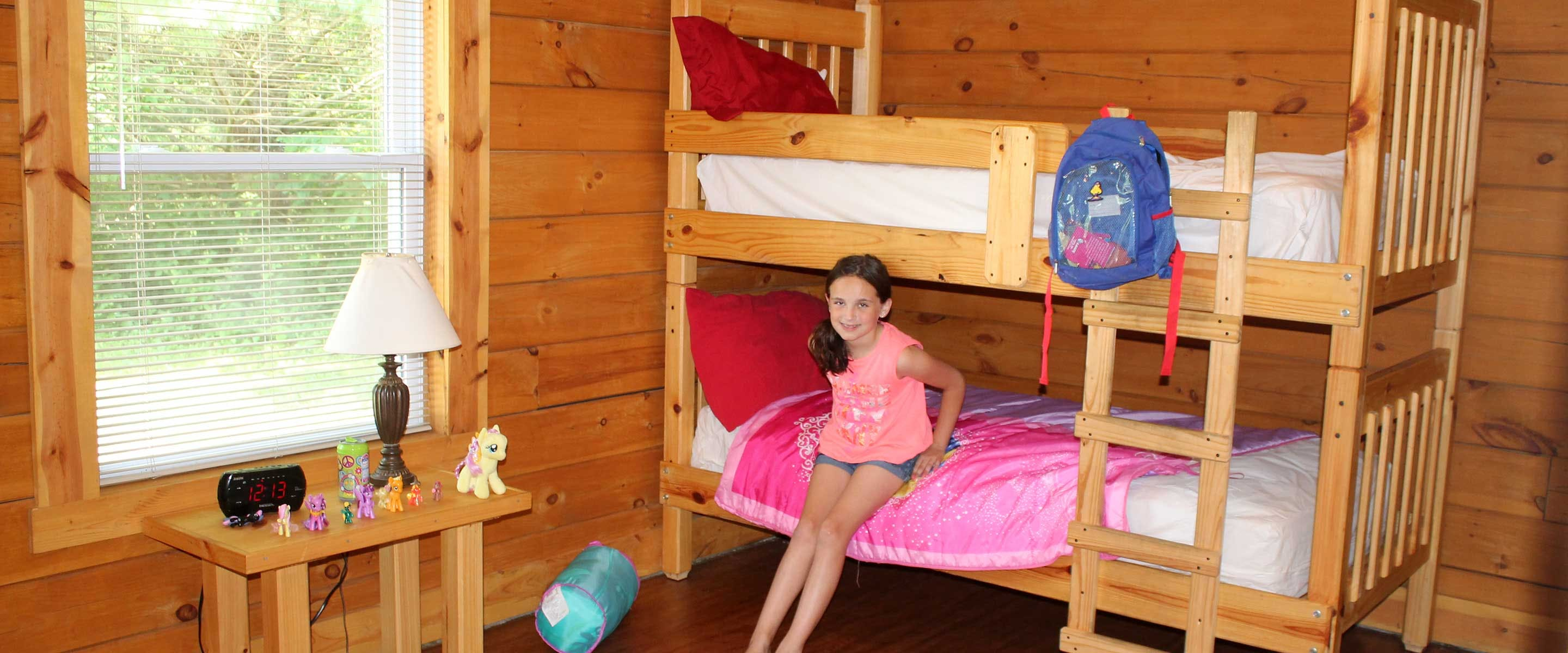 girl leading against bunk bed in cabin