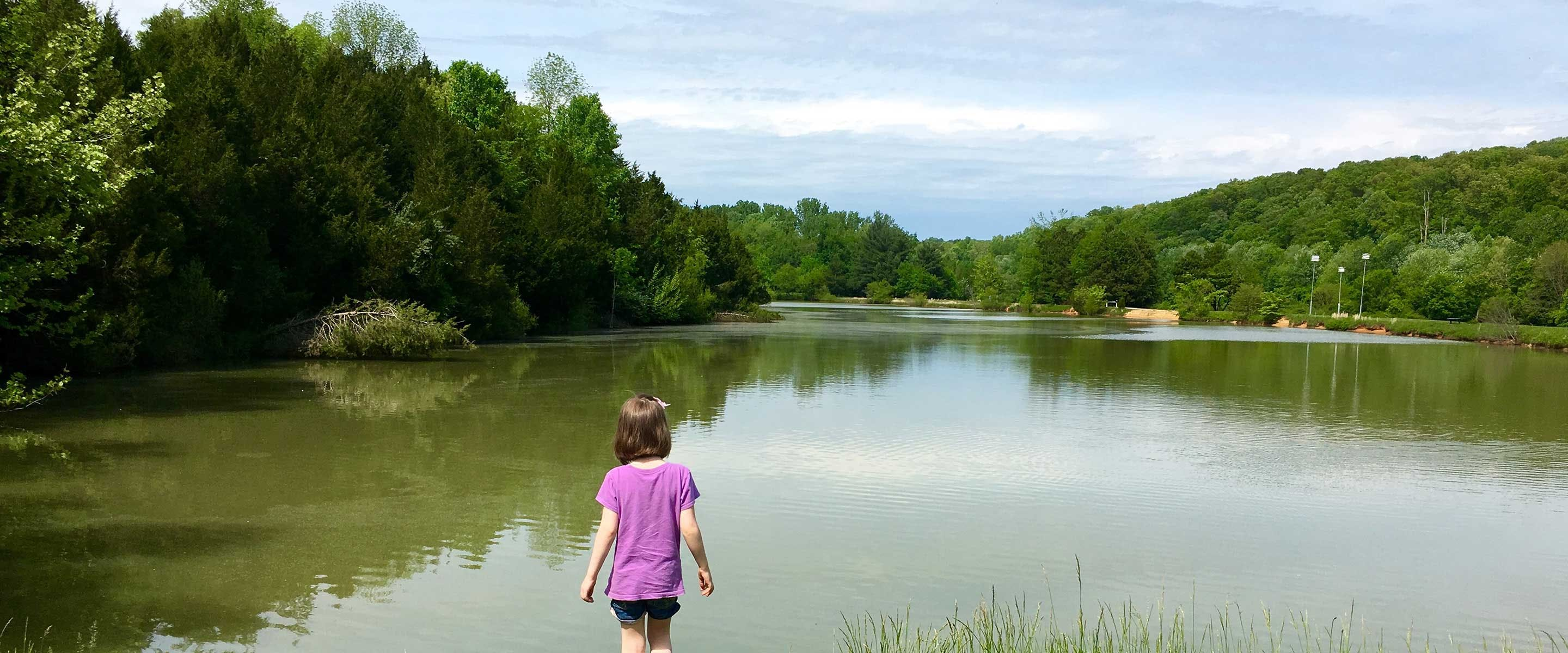 girl standing with her back to shop looking out over a beautiful serene lake at Hayswood Nature Preserve
