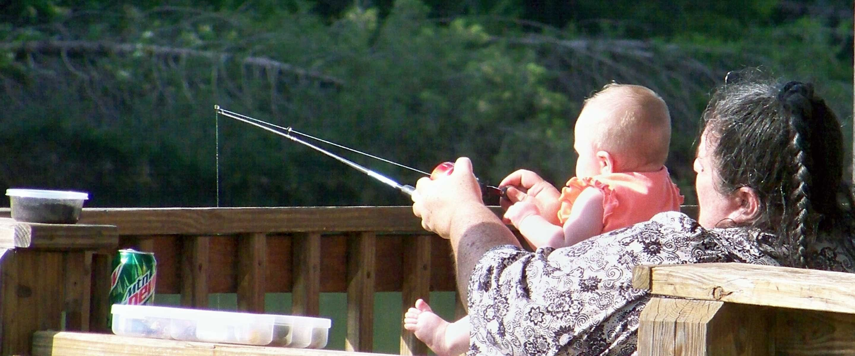 man fishing with baby in his lap