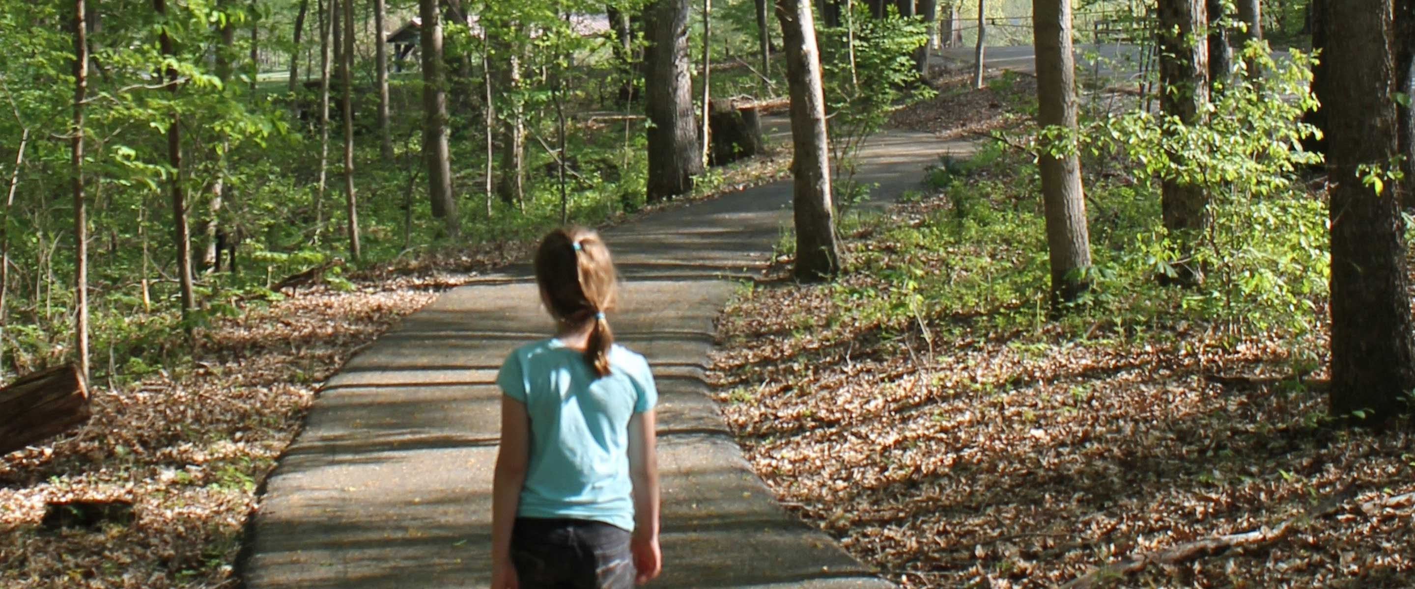 girl walking on paved nature trail to tree forrest canopy area in shade