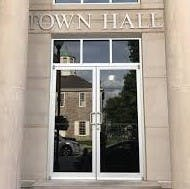 Front door of the Town Hall with reflection of First State Capitol in the glass doors of the Town Hall
